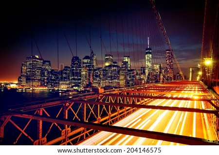 Speeding cars on Brooklyn Bridge, Downtown Manhattan, New York. Night scene. Light trails. City lights. Urban living and transportation concept - stock photo