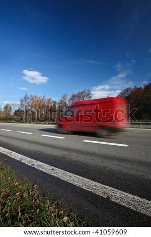 Speeding concept - Red van moving fast (speeding) on a highway - stock photo
