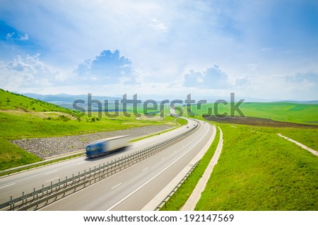 Speeding fast truck on a highway over the green hills on a sunny summer day with a bright blue sky suggesting quick and serious  transport delivery and shipping services - stock photo