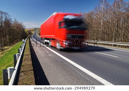 Speeding motion blur red truck on asphalt road in a rural landscape. Sunny day with blue skies. - stock photo