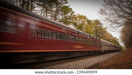 Speeding passenger train in motion in the tracks in North Carolina. A slow shutter speed was used in order to show the motion of the train - stock photo