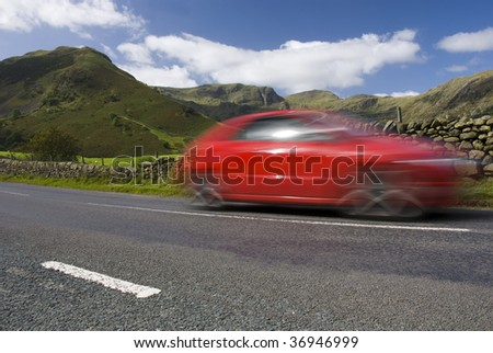 Speeding red car, Road A592,  Lake District National Park, UK - stock photo