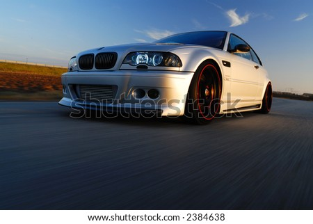 Speeding Silver Car in Golden Light - stock photo