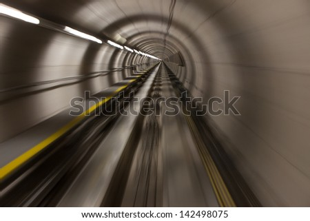 Speeding through a modern, stark tunnel fluorescent lights presents a visual vanishing point in the top center. The photo is an artistic, abstract view of high velocity transportation. - stock photo