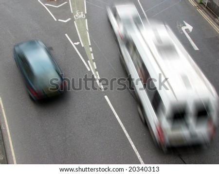 Speeding traffic at busy city road junction - stock photo