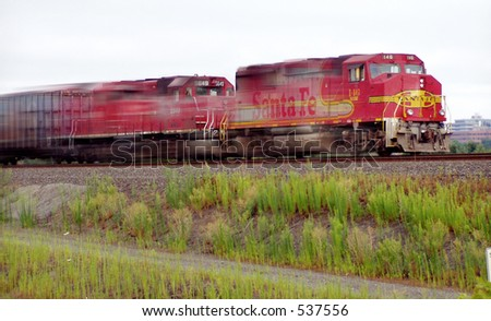 Speeding train in motion blur with two red engines surging to right -- city in distance
