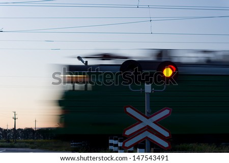 Speeding train passing a level crossing with a red signal in the foreground to prevent cars crossing the line - stock photo