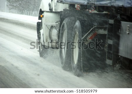 Speeding truck wheels on icy road during winter storm in Eastern Oregon