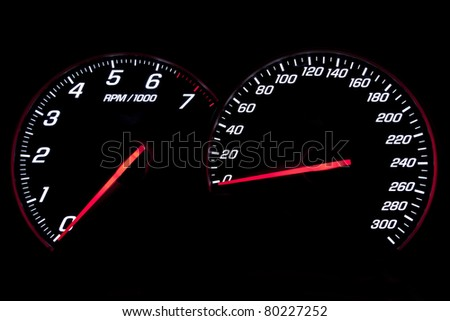 Speedometer and rev-counter on black background - stock photo