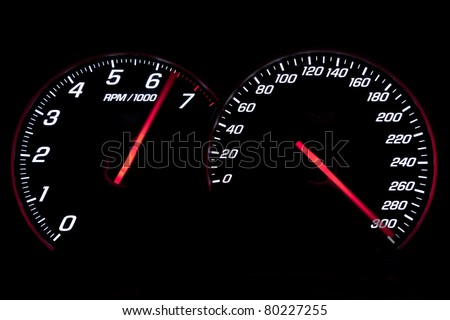 Speedometer and rev-counter reaching their limit on black background - stock photo