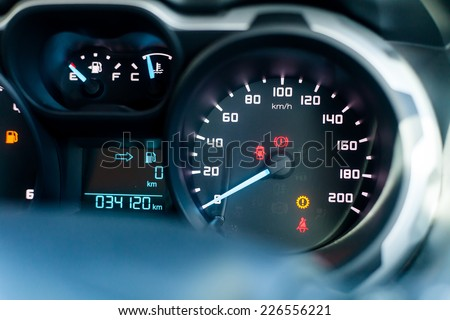 Speedometer in parked car, with LCD display of odometer and trip calculator, and fuel gauge empty - stock photo
