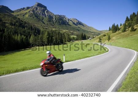Speedy motorbike on mountain road - Dolomites, Italy. - stock photo