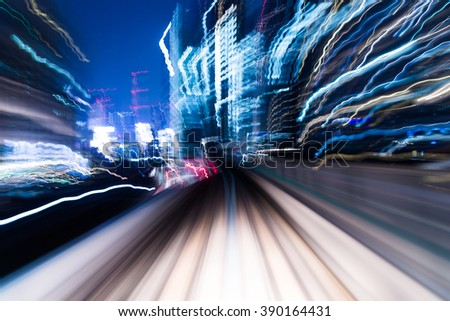 Speedy train passing though in city at night - stock photo