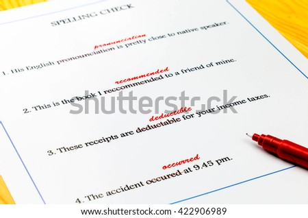 spelling sheet on table with red pen - stock photo