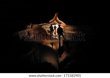 Spelunkers exploring a mystic cave river  - stock photo