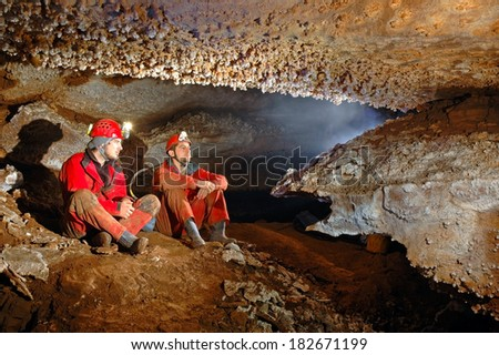 Spelunkers in cave admiring the stalactites - stock photo