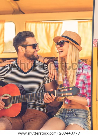Spending carefree time together. Handsome young man sitting in minivan and playing guitar while his girlfriend bonding to him and smiling - stock photo