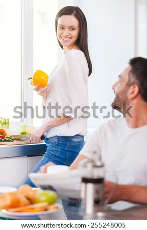 Spending good morning together. Beautiful young couple spending time in the kitchen together  - stock photo