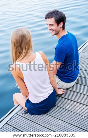 Spending good time together. Top view of beautiful young loving couple sitting at the quayside together and looking at each other with smile - stock photo