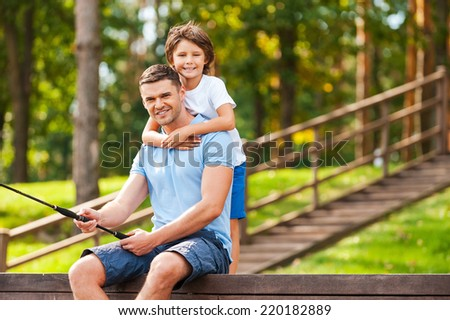 Spending good time with father. Happy father and son fishing together and smiling while sitting on quayside - stock photo