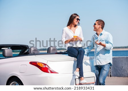Spending great time together. Beautiful young couple talking and smiling while standing near their new convertible  - stock photo