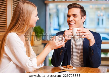 Spending great time together. Beautiful young couple talking to each other and smiling while enjoying coffee in cafe together  - stock photo