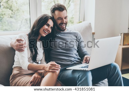 Spending great time together. Beautiful young loving couple looking at laptop and smiling while sitting together on the couch  - stock photo