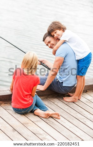 Spending great time together. Happy father fishing with his kids while sitting at the riverbank together - stock photo