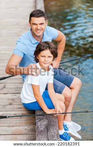 Spending great time together. Top view of father and son looking at camera and smiling while sitting at the quayside with fishing rods laying near them - stock photo