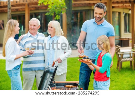 Spending great time with family. Happy family of five people barbecuing meat on grill on the back yard - stock photo