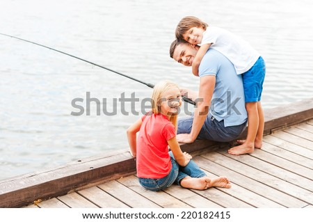 Spending great time with father. Happy father fishing with his kids while sitting at the riverbank together - stock photo