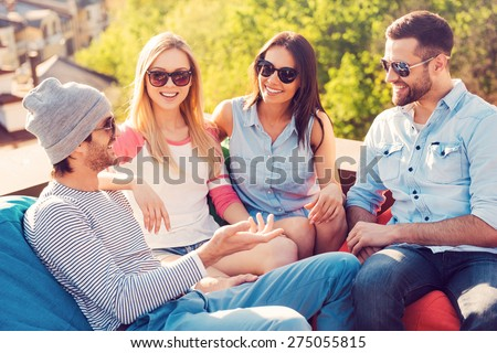 Spending great time with friends. Top view of four young cheerful people chatting while sitting at the bean bags on the roof of the building - stock photo