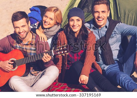 Spending great time with friends. Top view of four young happy people sitting near the tent together while young handsome man playing guitar and smiling - stock photo