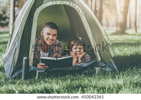 Spending quality time together. Father and son reading book and smiling while lying in tent together - stock photo