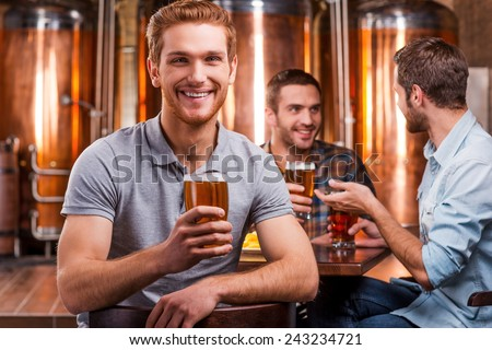 Spending time in beer pub. Handsome young man toasting with beer and smiling while his friends talking in the background  - stock photo