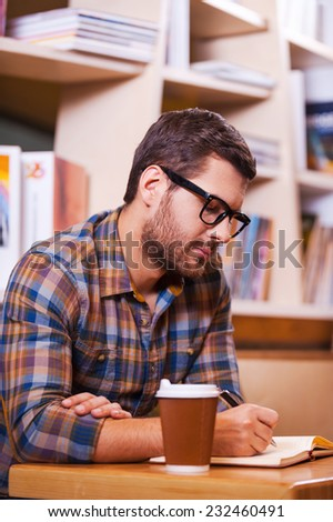 Spending time in library. Confident young man writing something in note pad while sitting at the desk in library - stock photo
