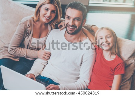 Spending time together. Top view of happy family of three bonding to each other and smiling while surfing the net together at home - stock photo