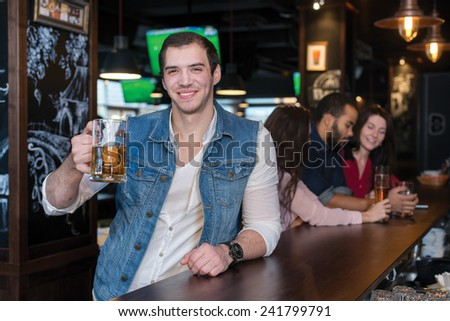 Spending time with beer. Portrait of young handsome man who is standing in a pub with glass of beer and smiling. His friends are standing on the background - stock photo