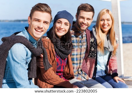 Spending time with best friends. Group of young happy people bonding to each other and smiling while sitting at the riverbank - stock photo
