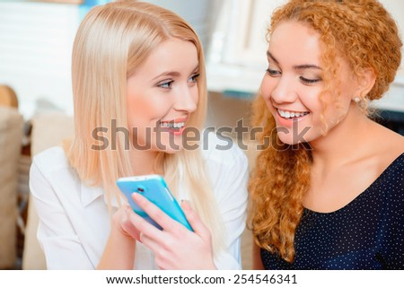 Spending time with friends. Two beautiful young women looking at the mobile phone and smiling while sitting on the couch of the cafe  - stock photo