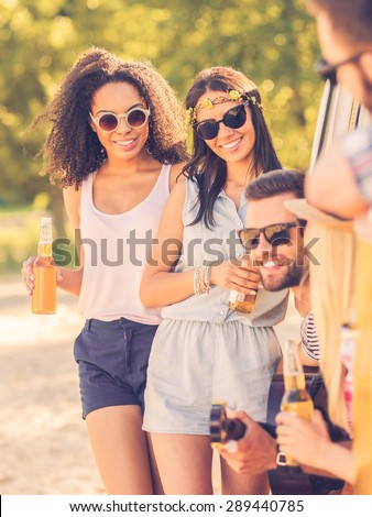 Spending time with friends. Two smiling young women standing near minivan while three people sitting inside it - stock photo