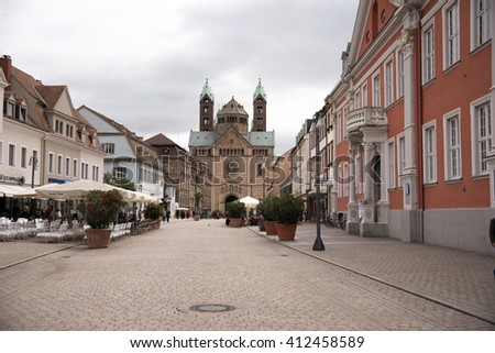Speyer, Germany - June  21, 2015: Tourists walk in the mainstreet flanked with historical buildings and the great cathedral in the old centre of Speyer, Germany on June 21, 2015