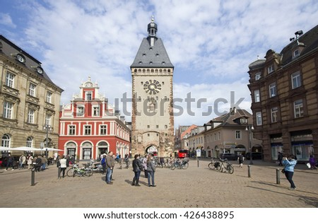 Speyer, Germany - May 2, 2014: Tourists walk and make pictures in the plaza in front of the old clock tower and a red house in the old centre of Speyer, Germany on May 2, 2014