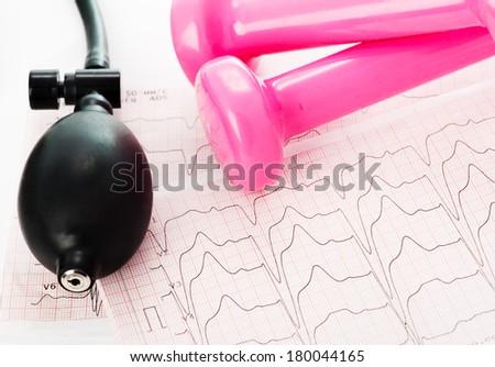 Sphygmomanometer and pink dumbbells lying on ECG diagram - stock photo