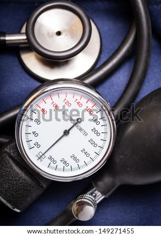 Sphygmomanometer and stethoscope on a dark blue background - stock photo