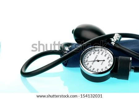 Sphygmomanometer on blue, reflective background  - stock photo