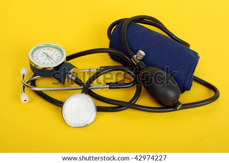 sphygmomanometer stethoscope blood pressure on yellow background - stock photo
