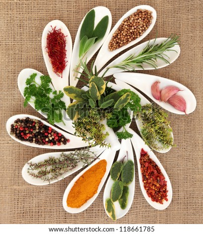 Spice and fresh herb selection in porcelain dishes and mortar with pestle over hessian background. - stock photo