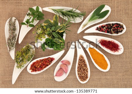 Spice and herb leaf selection in porcelain dishes and mortar with pestle over hessian background. - stock photo
