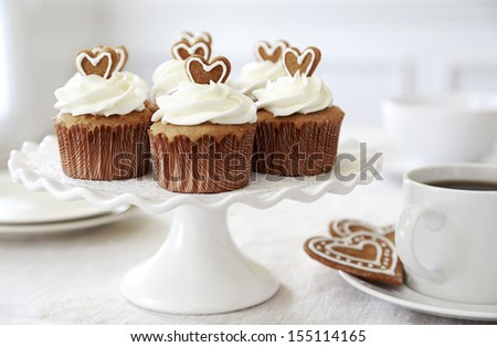 Spice cupcakes with creamcheese frosting desorated with a gingerbread heart. - stock photo